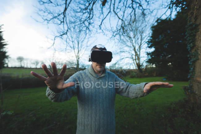 Homme utilisant casque de réalité virtuelle dans la forêt à la campagne — Photo de stock