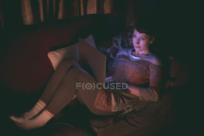 Frau benutzt Laptop auf Sofa im heimischen Wohnzimmer — Stockfoto