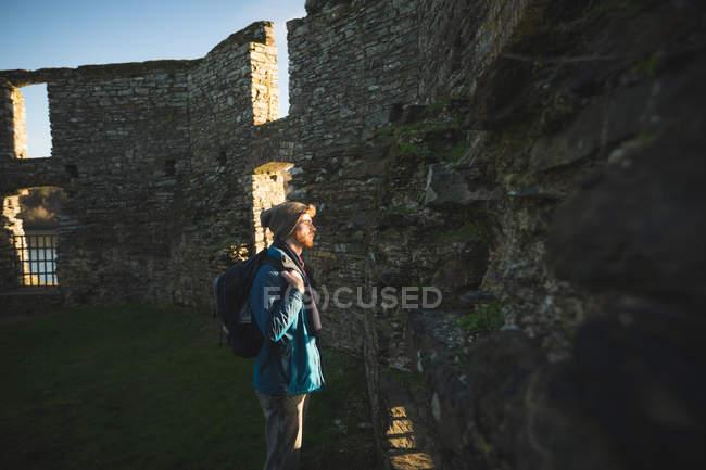 Молодой турист, стоящий в старых руинах в сельской местности под солнечным светом — стоковое фото