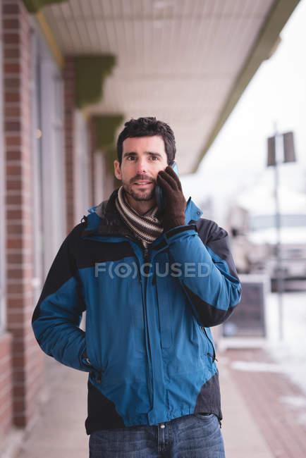 Мужчина разговаривает по мобильному телефону на городской улице зимой . — стоковое фото