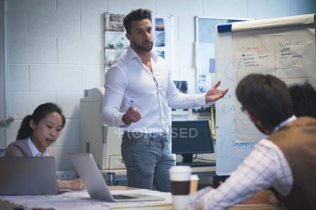 Exécutif à collègue adonnant présentation chevalet de bureau — Photo de stock