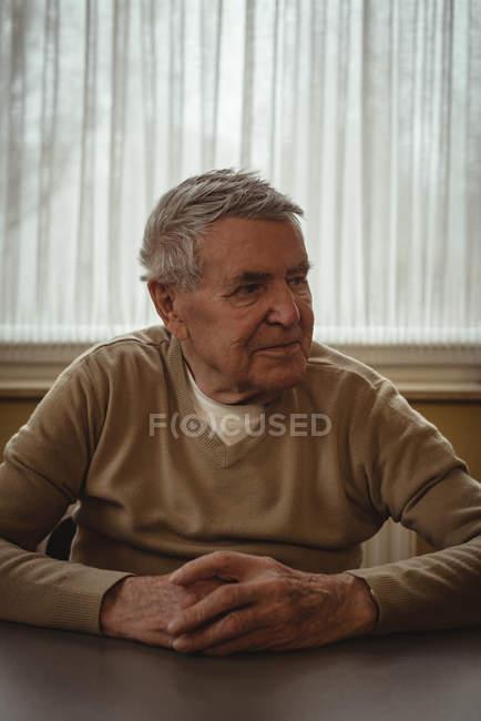 Homme âgé assis à une table à la maison — Photo de stock