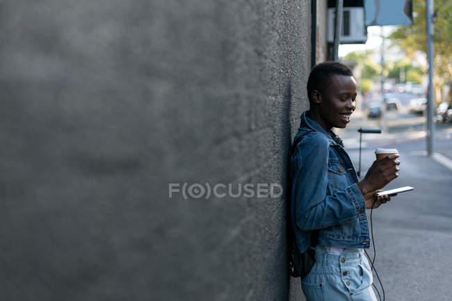 Frau beim Kaffeetrinken mit Handy gegen Wand — Stockfoto