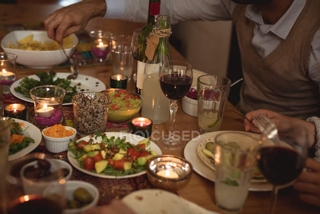 Cropped image of friends having meal at table — Stock Photo