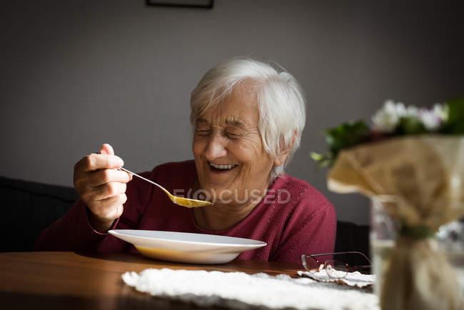 Smiling senior woman having breakfast at home — Stock Photo