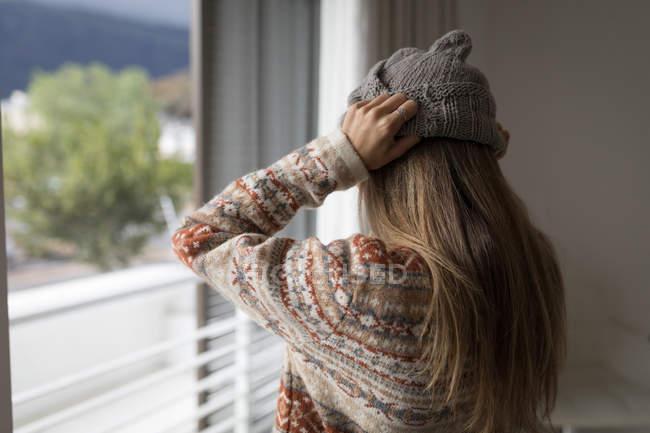 Вид сзади на женщину в шерстяной шляпе в гостиной дома . — стоковое фото
