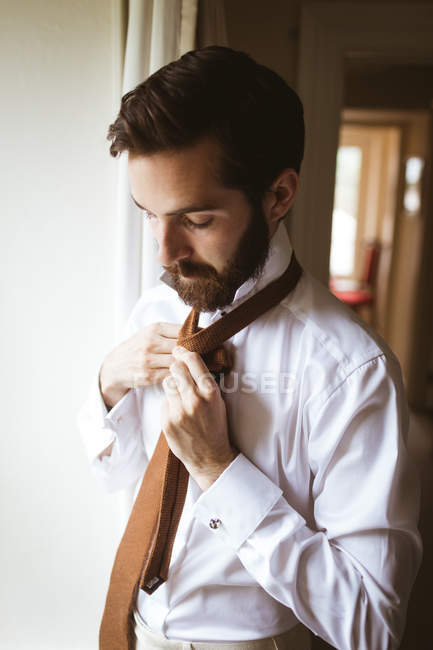 Close-up of handsome man tying his tie — Stock Photo