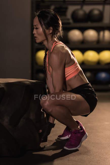 Подходящая женщина, тренирующаяся с тяжелой шиной в фитнес-студии — стоковое фото