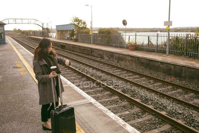 Female executive waiting for train with luggage at railway platform — Stock Photo
