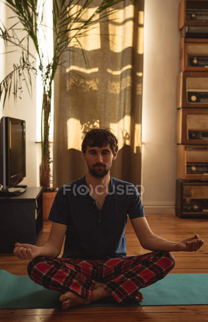 Man practicing yoga in living room at home — Stock Photo