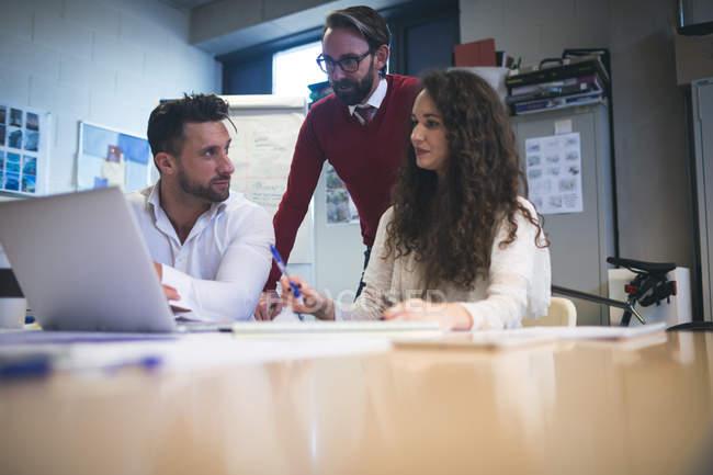 I dirigenti discutono sopra computer portatile in ufficio moderno — Foto stock