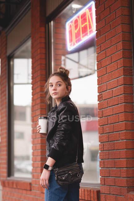 Fille réfléchie debout avec verre jetable à l'extérieur du centre commercial — Photo de stock