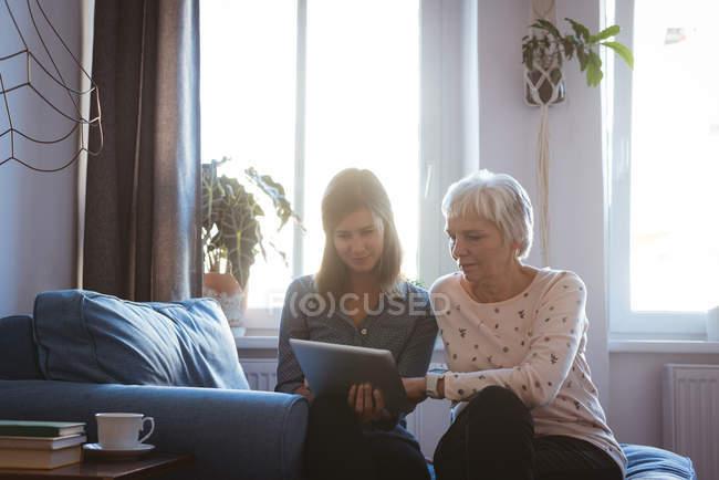Ältere Frau und Tochter mit einer Registerkarte bei der Standortwahl auf dem Sofa während des Tages — Stockfoto