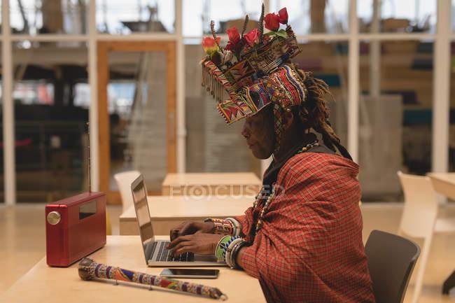 Масаї людина в традиційному одязі, використовуючи ноутбук у торговий центр — стокове фото