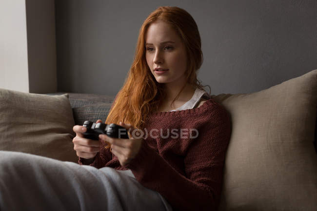 Young woman playing video games at home — Stock Photo