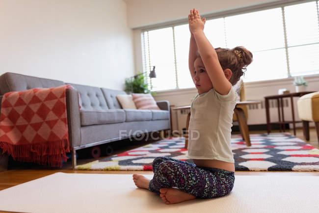 Niedliche Mädchen Yoga im Wohnzimmer zu Hause durchführen — Stockfoto