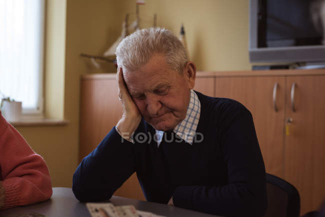 Angespannter Senior spielt Karte im Pflegezimmer — Stockfoto