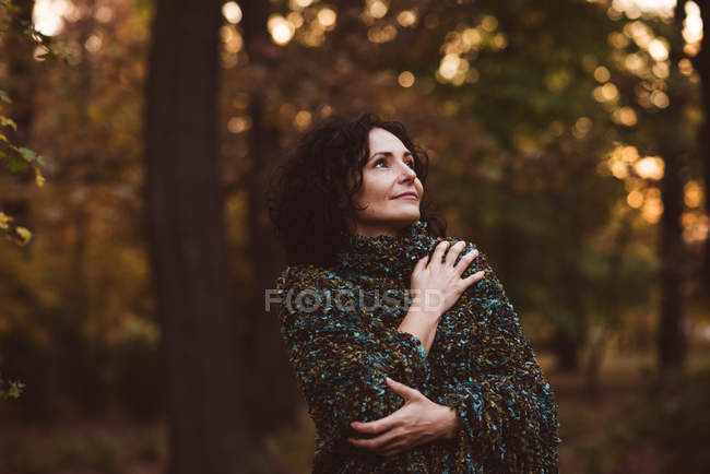 Smiling mature woman standing in forest — Stock Photo
