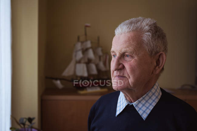 Thoughtful senior man standing at nursing home — Stock Photo