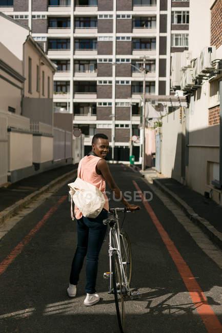 Femme avec vélo dans la rue de la ville par une journée ensoleillée — Photo de stock