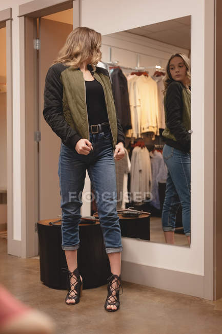 Beautiful girl checking jacket in front of the mirror at shopping mall — Stock Photo