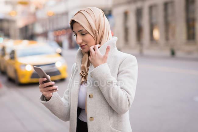 Mujer en hijab usando teléfono móvil en la calle de la ciudad - foto de stock