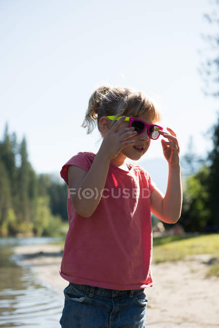 Cute girl wearing sunglasses near river bank on a sunny day — Stock Photo