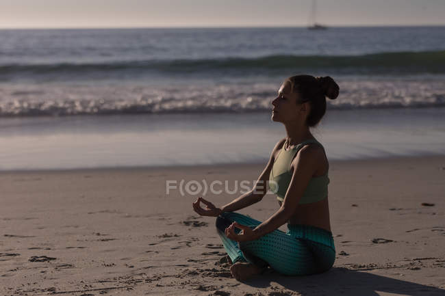 Fit femme méditant sur la plage de sable au crépuscule . — Photo de stock