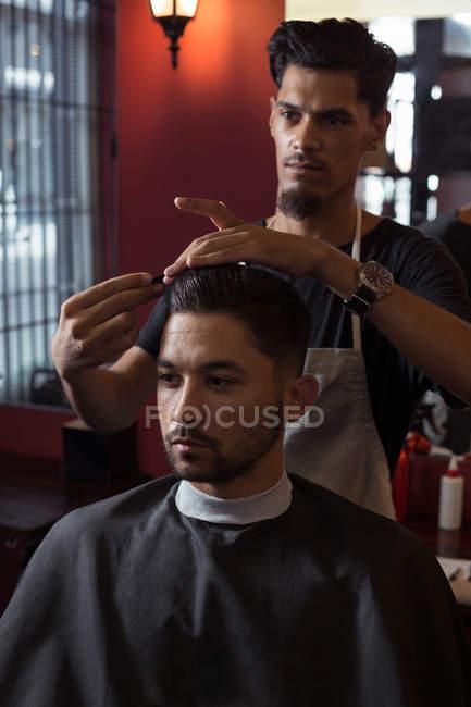 Hombre recibiendo su pelo recortado con tijera en la barbería - foto de stock