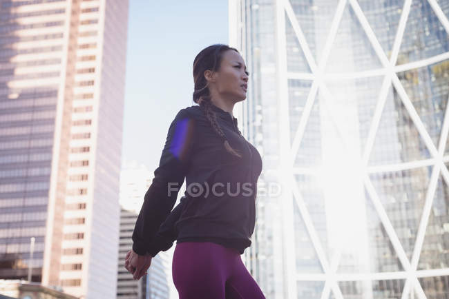 Fit femme échauffement contre la construction par une journée ensoleillée — Photo de stock