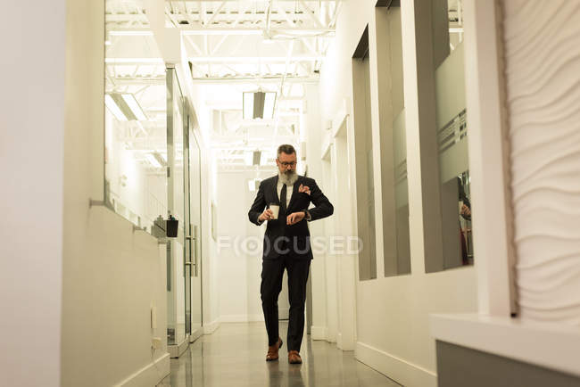 Business executive looking at smartwatch while having coffee in office corridor — Stock Photo