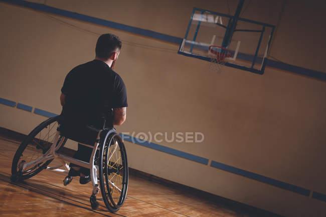 Інвалідів чоловік дивиться на баскетбольне кільце в суді — стокове фото