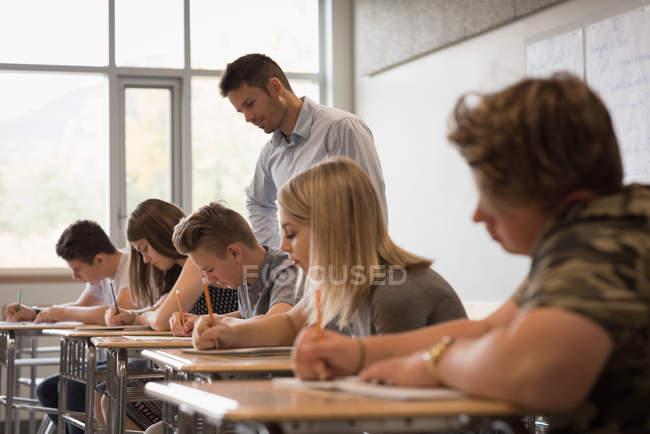 Lehrer, die Unterstützung der Studenten in ihren Studien im Klassenzimmer — Stockfoto