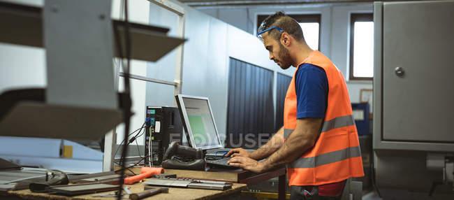 Чоловічий працівник працює на комп'ютері на заводі — стокове фото
