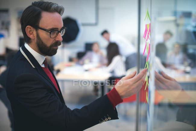 Business executive guardando appunti appiccicosi in ufficio — Foto stock