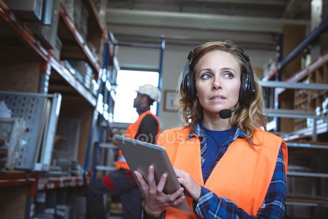Arbeiterin nutzt digitales Tablet in Fabrik — Stockfoto