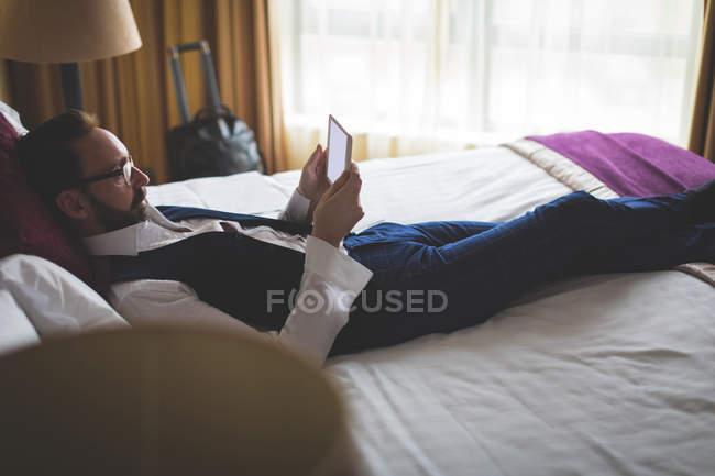 Businessman using digital tablet in bedroom at hotel — Stock Photo