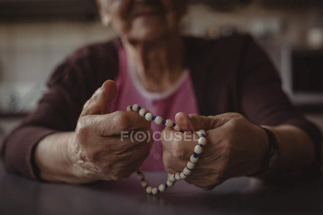 Close-up of senior mujer Rosario en casa - foto de stock