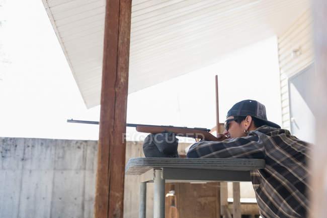 Homem apontando a arma no alvo no tiro ao alvo em um dia ensolarado — Fotografia de Stock