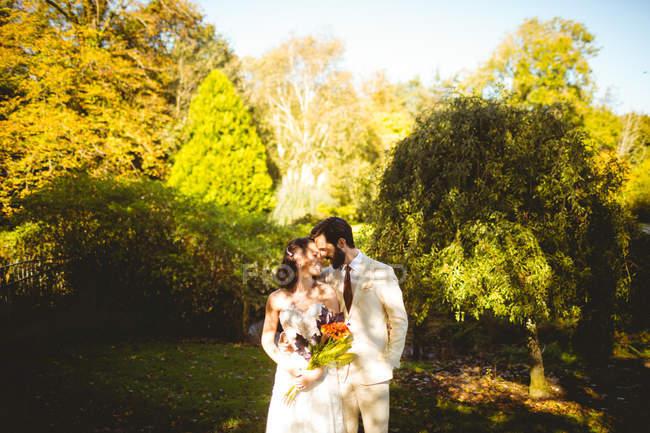 Novia romántica y el novio abrazando unos a otros en el jardín - foto de stock