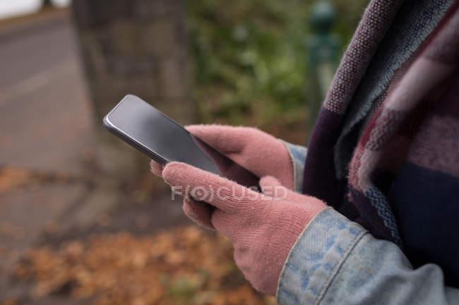 Крупный план средней части молодой женщины, использующей мобильный телефон в парке — стоковое фото