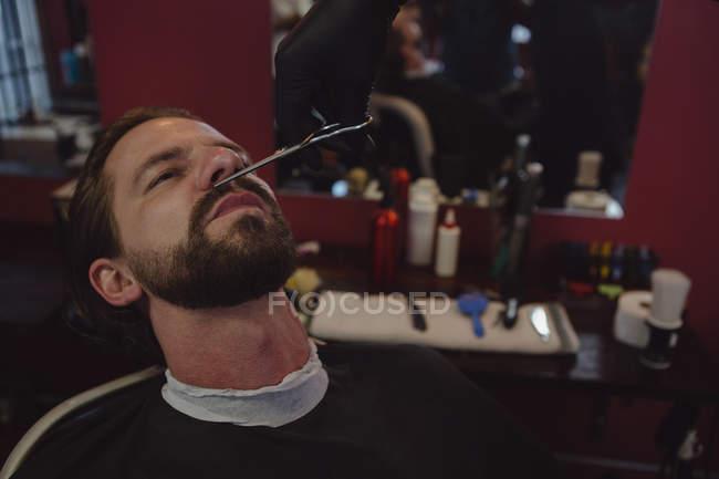 Al hombre le cortan la barba con tijeras en la barbería. - foto de stock
