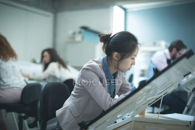 Female executive working over drafting table in modern office — Stock Photo
