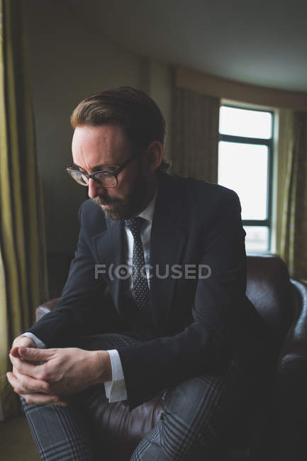Businessman sitting on arm chair in hotel room — Stock Photo