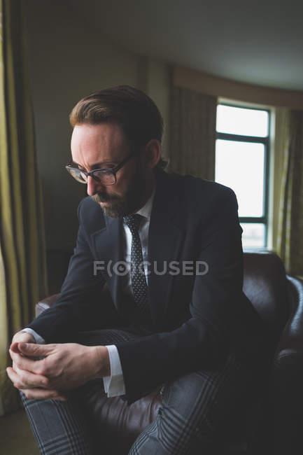 Empresário, sentado na cadeira de braço em quarto de hotel — Fotografia de Stock