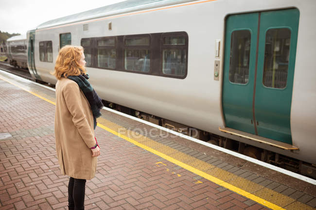 Young woman standing on platform in front of running train on a rainy day — Stock Photo
