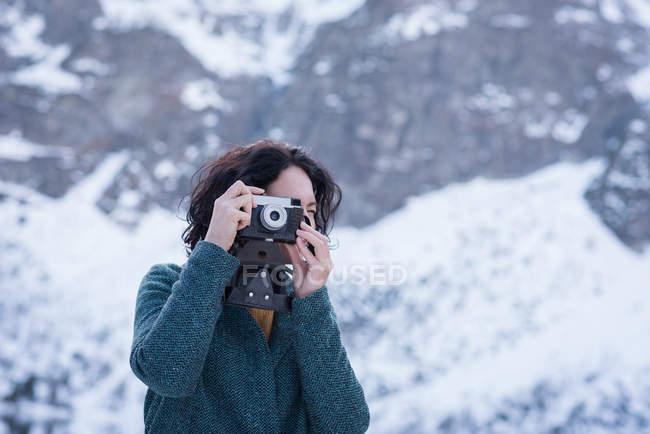 Жінка беручи фотографію з цифрової камери протягом зими — стокове фото