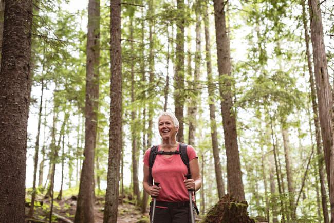 Улыбающаяся взрослая женщина с походными столбами, стоящая в лесу — стоковое фото