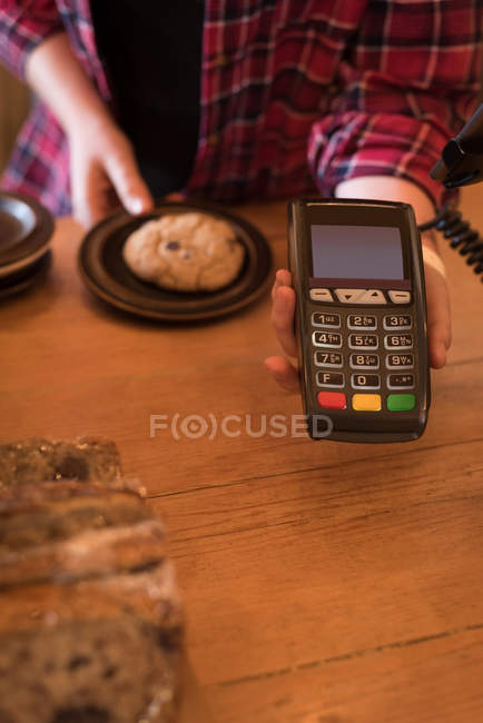 Mid section of woman holding payment terminal at counter in cafe — Stock Photo
