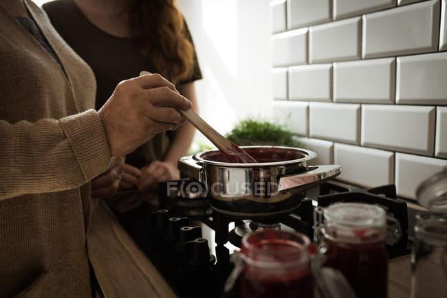 Mitte Abschnitt Großmutter und Enkelin Himbeermarmelade in Küche zu Hause kochen — Stockfoto